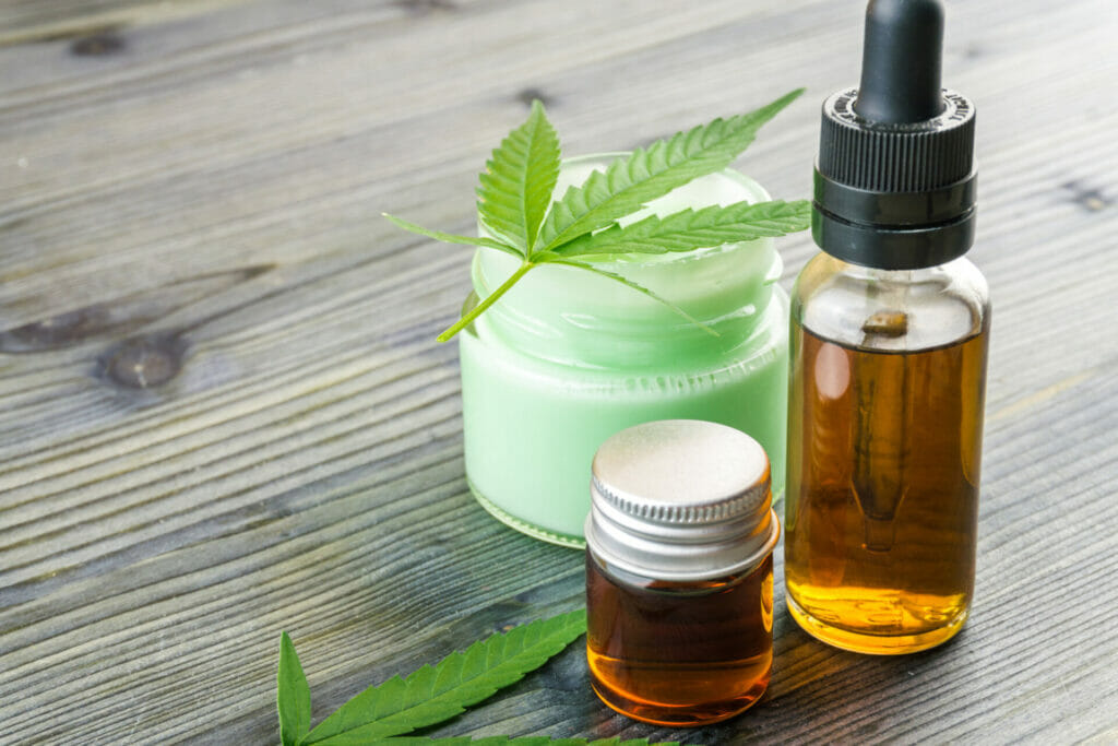 cannabis cbd oils in glass bottle and cbd lotion gel little jars with hemp leafs on table