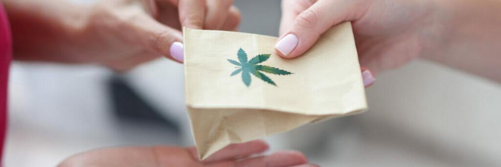 handing over paper bag with marijuana sign.